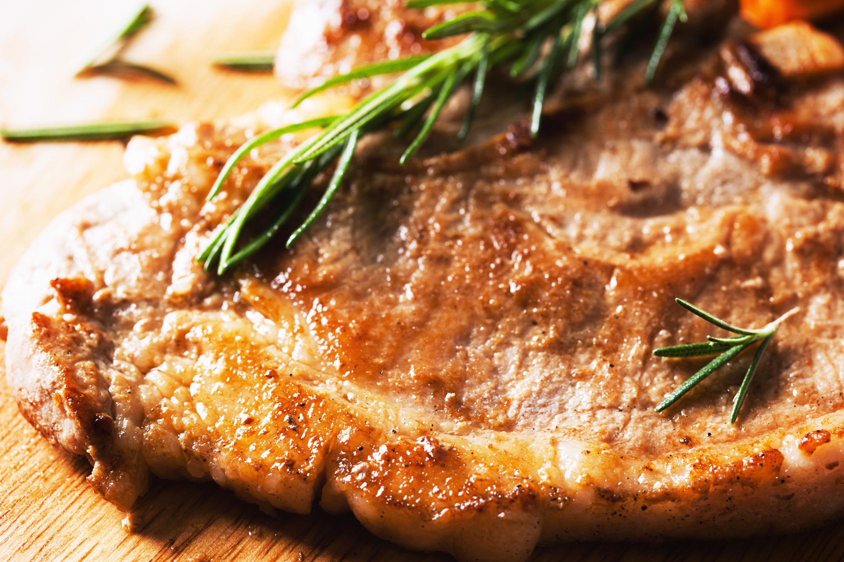grilled pork chop on wooden board